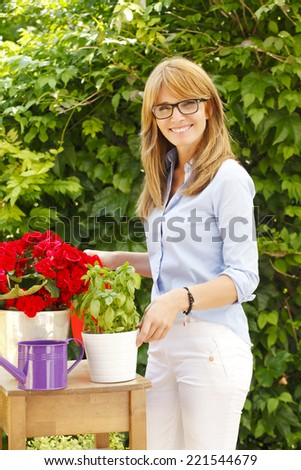 Small flower shop owner standing at desk and working in her store. Small business.  - stock photo