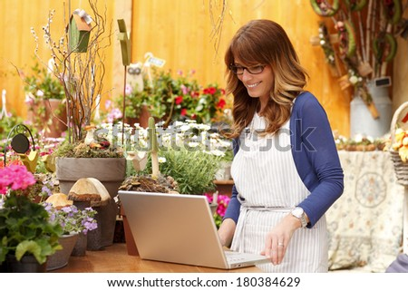 Small flower shop owner working on laptop in her shop. - stock photo