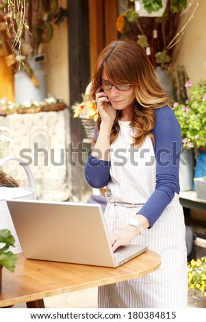 Small flower shop owner working on laptop in her shop and making call. - stock photo