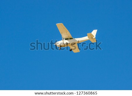 Small flying aircraft in a blue sky - stock photo