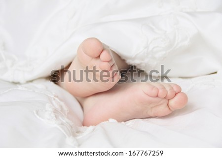 small foot sleeping baby in the crib