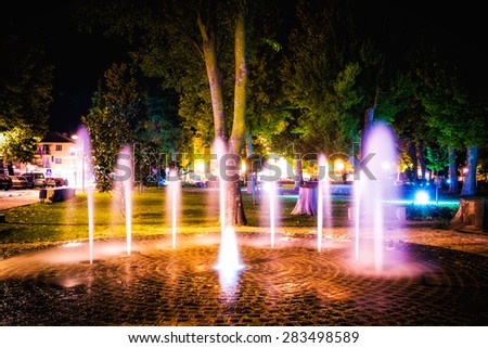Small fountain in the city park on a summer night - stock photo