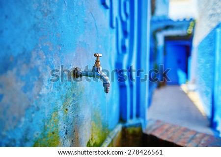 Small fountain with drinkable water on a street in Medina of Chefchaouen, Morocco, small town in northwest Morocco known for its blue buildings - stock photo