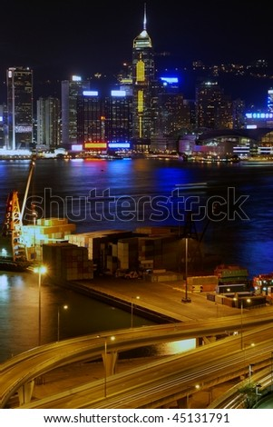 Small freight terminal in Kowloon side with view of the skyline of Hong Kong island, at night - stock photo