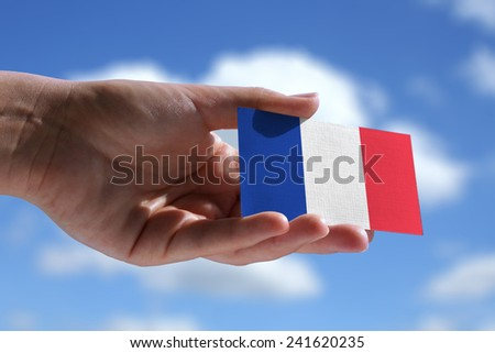 Small French flag against sky with cumulus clouds - stock photo