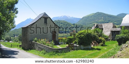Small french village in the valley with green grass surrounding by mountains - France - The Pyrenees - Panorama. - stock photo