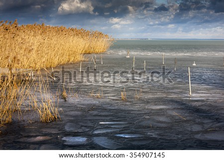 Small frozen flat-boat harbor on the lake in Hungary - stock photo