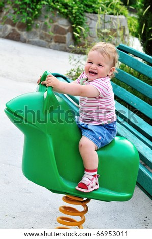 Small funny girl girl on spring frog swing