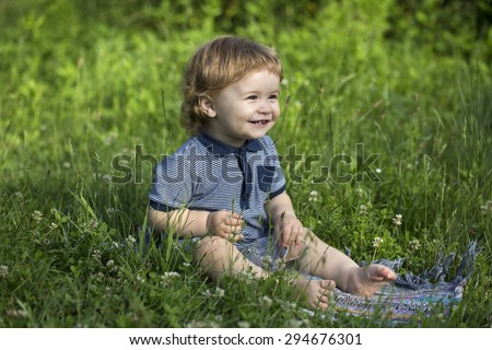 Small funny happy smiling baby boy sitting in meadow on fresh green grass with glass cup, horizontal picture - stock photo