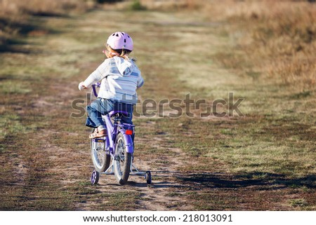 Small funny kid riding bike with training wheels. - stock photo