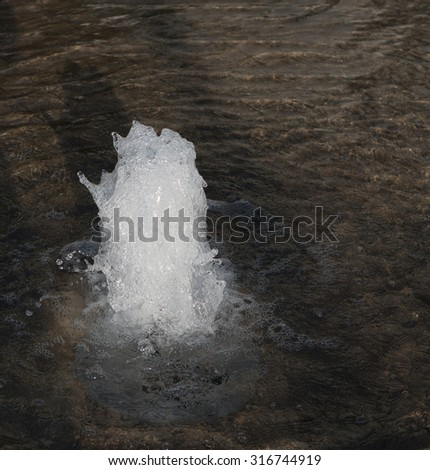 Small geyser in clear transparent sea with waves