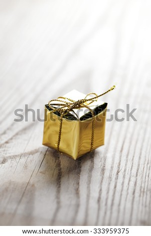 Small gift box on wooden background macro close-up - stock photo