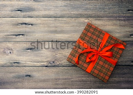 Small gift box with red ribbon on wooden table