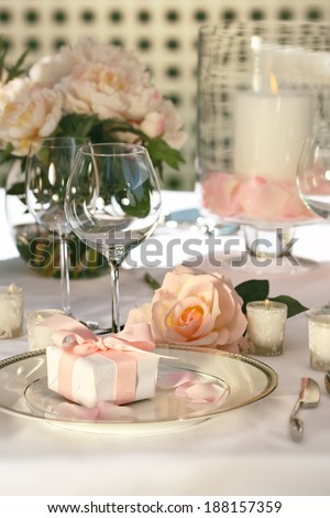 Small gift on plate at wedding reception - stock photo