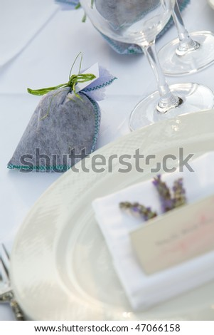 Small gift on table with a wine glass and plate - stock photo