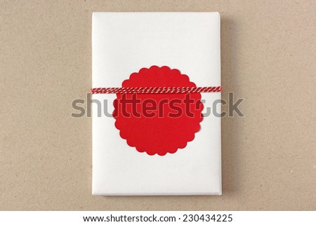 Small gift with red gift tag and twine on brown kraft paper background with space for your text - stock photo
