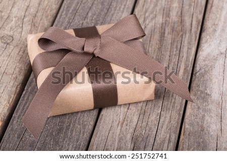 Small gift wrapped in brown paper, ribbon and bow on old wood boards - stock photo