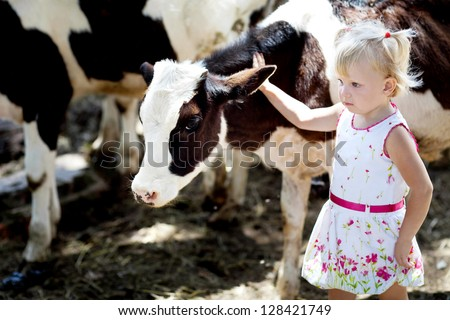 small girl and a cow - stock photo