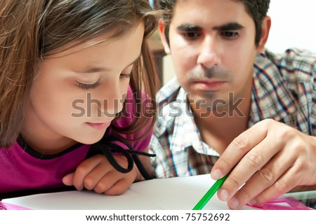 Small girl and her young latin father working on a school project at home