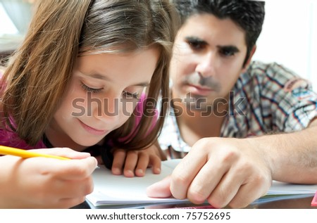 Small girl and her young latin father working on a school project at home - stock photo