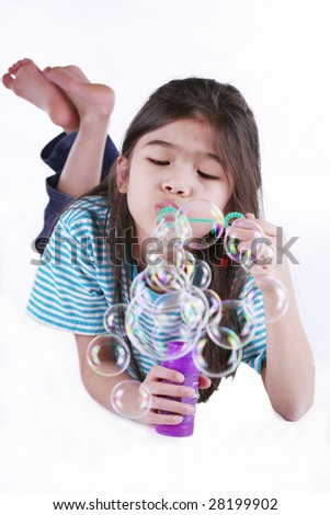 Small girl blowing bubbles lying on floor, part asian - Scandinavian descent