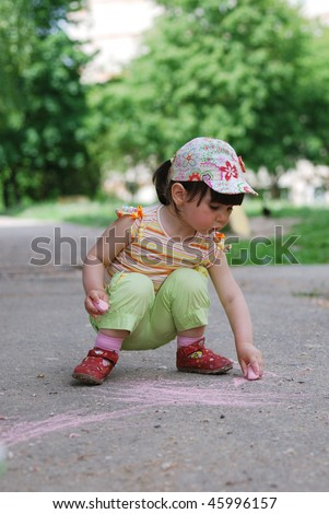 small girl drawing on the sidewalk with chalk - stock photo