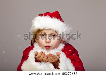 Small girl dressed as santa claus blows snow flakes from palm.  Isolated on white background. - stock photo