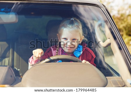 small girl driving a car - stock photo