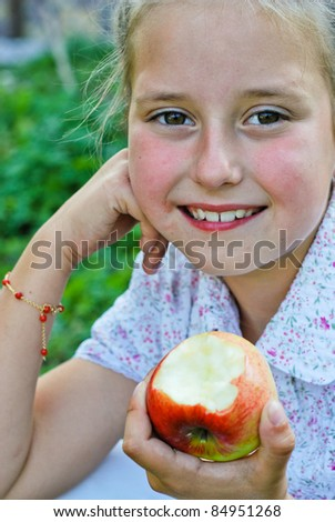 Small girl eating apples - stock photo