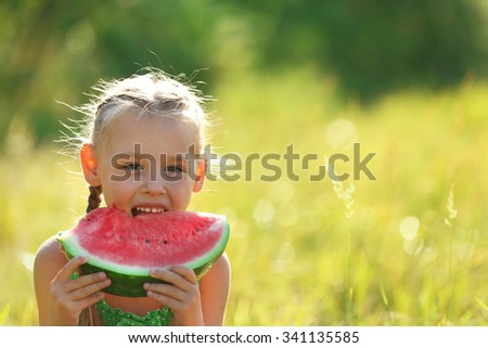 Small girl eating watermelons on lawn