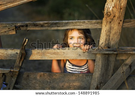 Small girl enjoy being behind an old wooden fence - stock photo