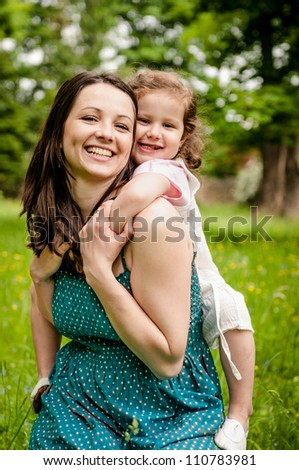 Small girl enjoying life with her mother outdoor - lifestyle portrait - stock photo