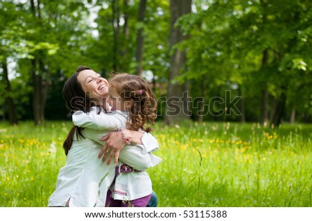 Small girl enjoying life with her mother outdoors - stock photo