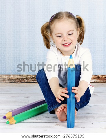Small girl holding big crayons - stock photo