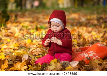 Small girl in autumn park playing with autumn leaves, vibrant autumn background