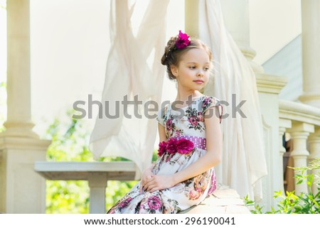 Small girl in colorful dress and flowers outdoor in the park. Facial expression.