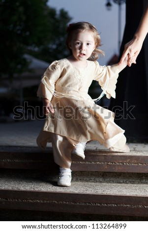 small girl in gothic dress descending steps and holding mom's hand