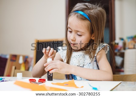 small girl in kindergarten doing an applique - stock photo