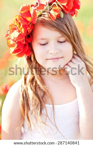 small girl in poppy wreath eating strawberry in the field. Picnic in Crimea