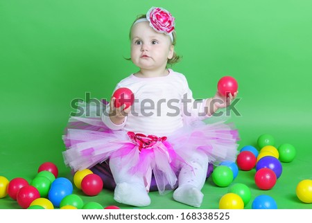 Small girl in rose suit on green background