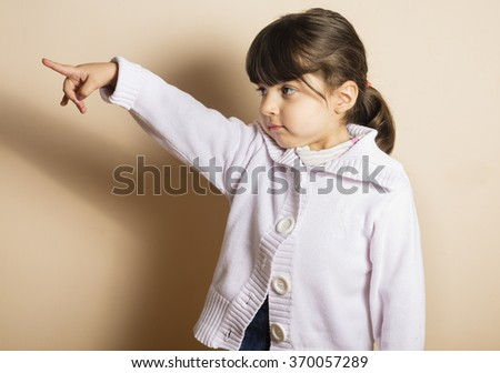 Small girl in studio pointing with her hand with off white background - stock photo