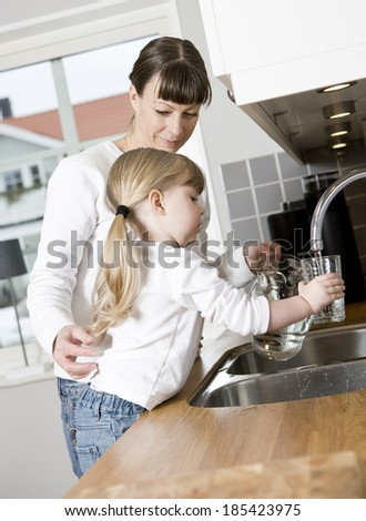 Small Girl in the kitchen with her mother drinking water - stock photo