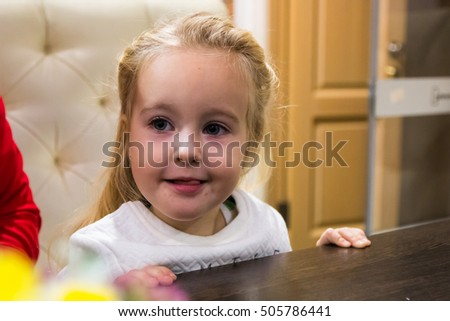 Small girl in white dress in restaurant