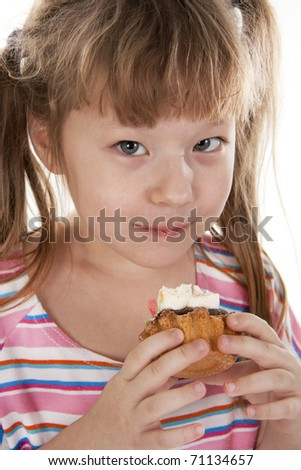 Small girl is eating cake - stock photo