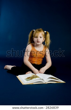 Small girl is reading a book - stock photo