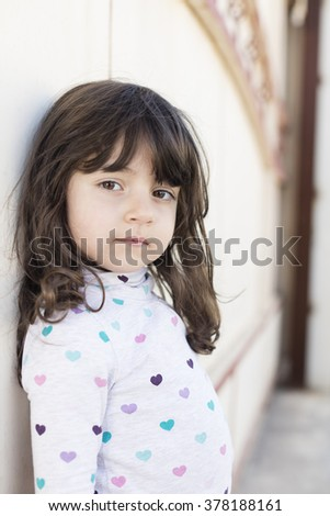 Small girl leaning on wall in Iraq