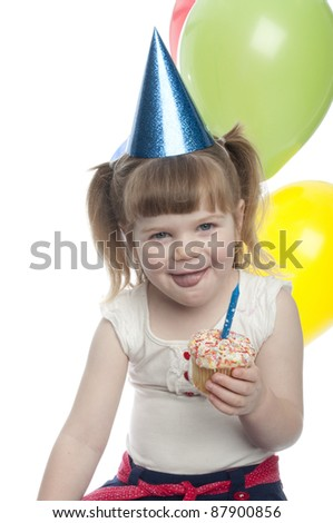 small girl licking lips over cup cake in hand. the cup cake has a candle in it