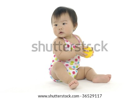 Small girl looking up with ball - stock photo