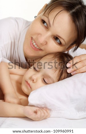 Small girl lying on bed at home with mom