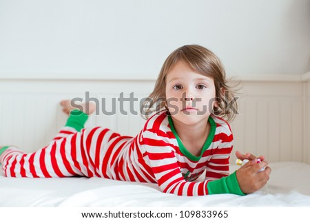 Small girl lying on her bed in striped pajamas - stock photo